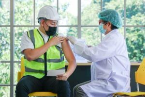 man in construction gear getting vaccine